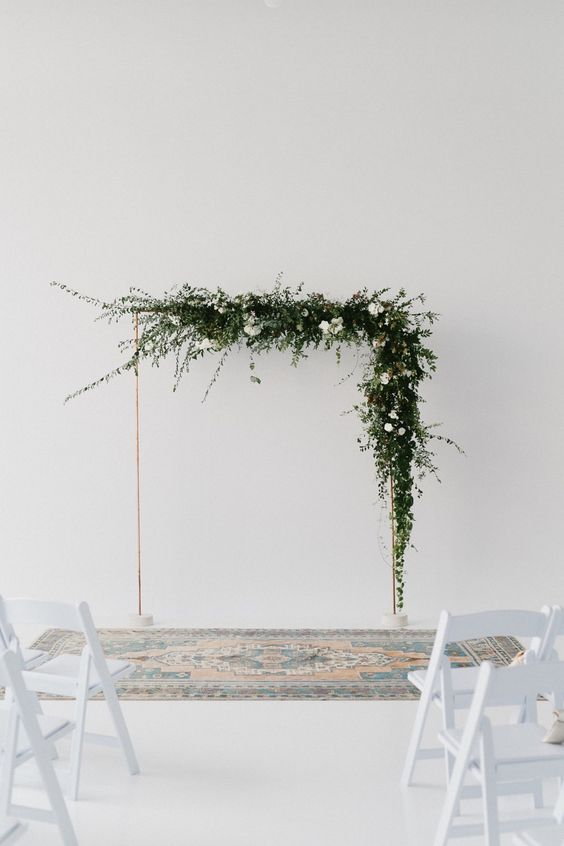 a gorgeous minimalist wedding arch decorated with lush greenery and white blooms plus a colorful rug is a cool and fresh idea