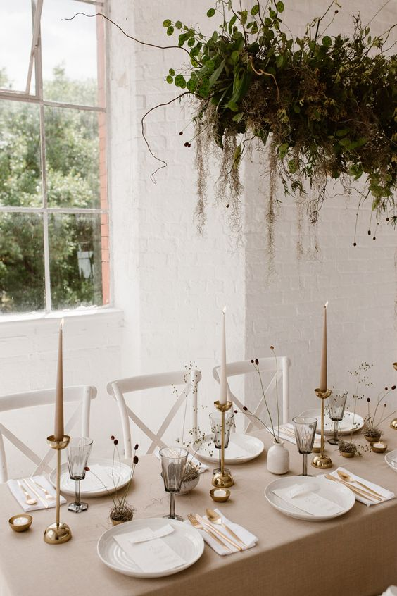 a gorgeous minimalist wedding tablescape with a greige tablecloth, greige candles, dried grasses, a greenery arrangement over the table
