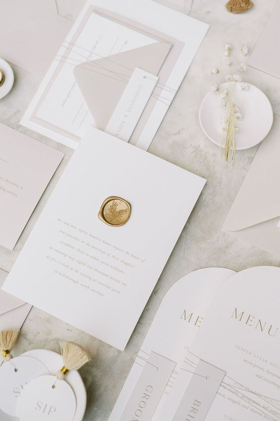 a gorgeous neutral minimalist wedding invitation suite with tan touches, neutral lettering, a gold stamp and curved menus