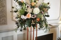 a gorgeous tall wedding centerpiece of white and peachy blooms, pampas grass, lots of greenery, seed pods, cotton and foliage on a copper stand