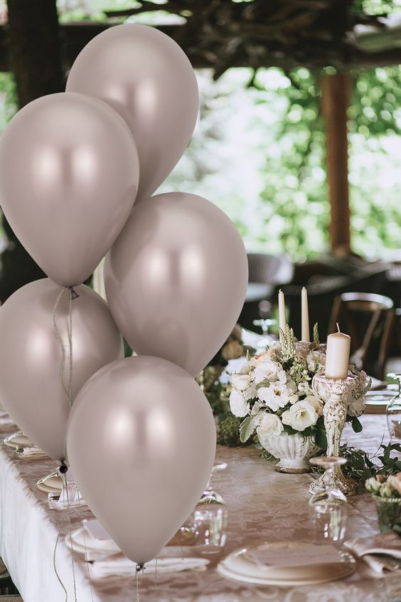 a greige floral print tablecloth, greige balloons, white blooms, white pilalr candles and greenery and white porcelain are chic