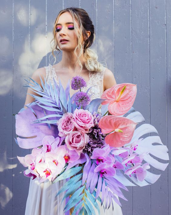 a jaw dropping iridescent wedding bouquet with colorful fronds, blooms and leaves, in purple, pink and blue is amazing