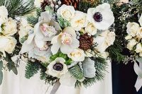 a large winter wedding bouquet of white blooms, evergreens, berries, pinecones and some grey ribbons is a lovely idea