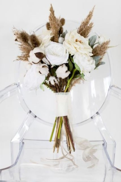 a lovely boho wedding bouquet of white and creamy blooms, cotton, pampas grass and greenery is a cool idea for a fall or winter wedding