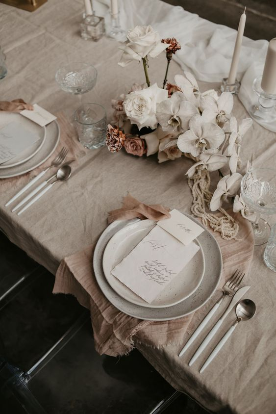 a lovely greige and blush wedding tablescape with beautiful and textural linens, white orchids and roses, neutral candles and speckled plates