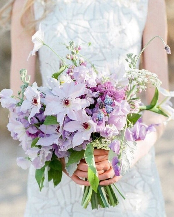 a lovely iridescent wedding bouquet with blush, purple and blue blooms and some foliage is a gorgeous idea