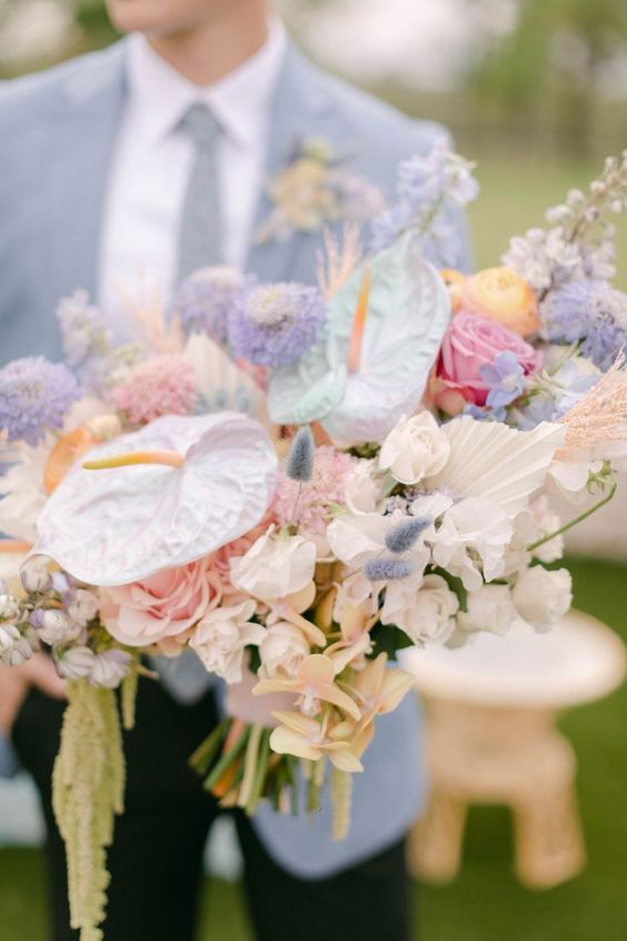a lovely iridescent wedding bouquet with fresh and dried blooms, leaves and grasses spray painted pink, lilac and iridescent is wow