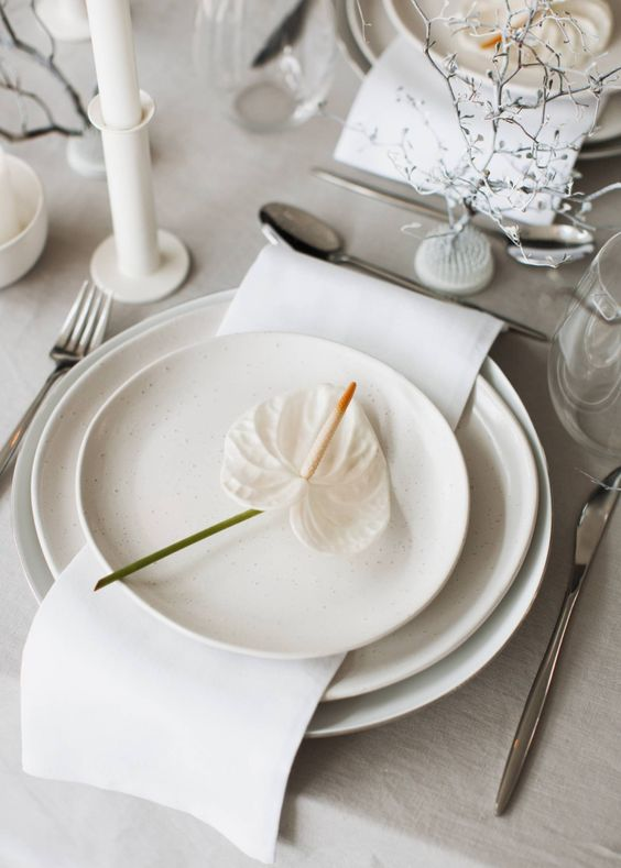 a lovely neutral wedding tablescape with all-neutral everything, with white candles in white candlesticks, elegant cutlery