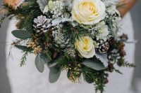 a lovely snowy winter wedding bouquet of white blooms, pale greenery, evergreens, pinecones, baby's breath and twigs is amazing