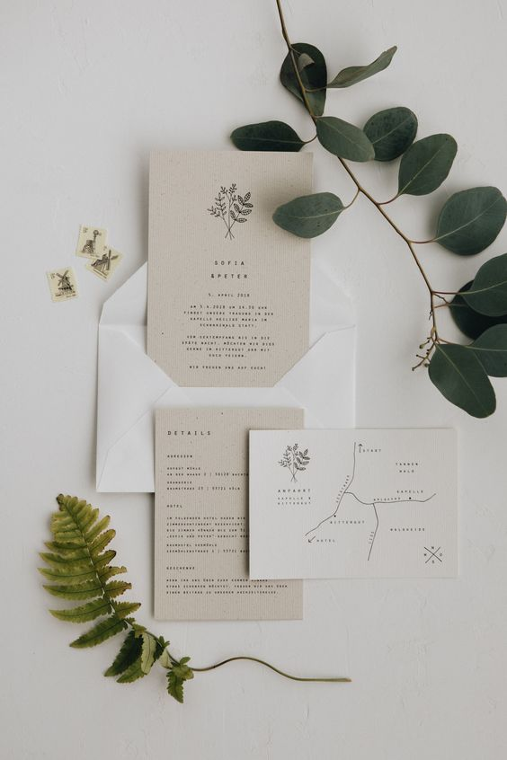 a lovely tan and white minimalist wedding invitation suite with small black lettering, a printed map and botanical prints and patterns