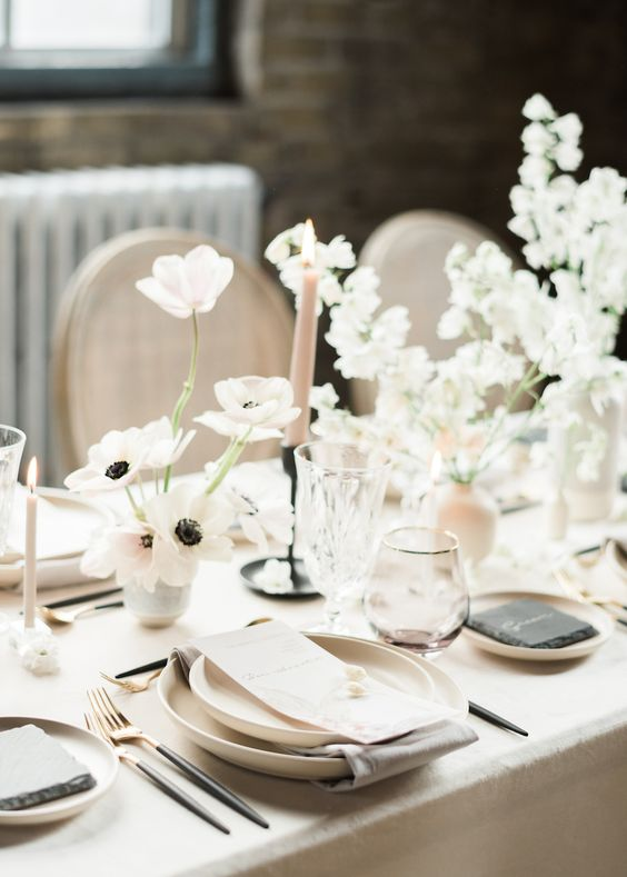 a minimalist and ethereal neutral wedding tablescape with neutral linens, plates, blush candles and white and blush floral arrangements