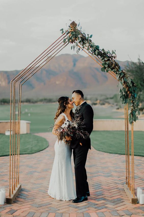 a minimalist copper wedding arch decorated with greenery will fit a modern, minimalist or boho wedding and looks stylish and simple