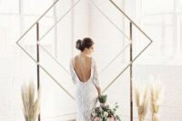 a minimalist double rhomb wedding arch and arrangements of pampas grass in vases around it for a minimalist boho wedding