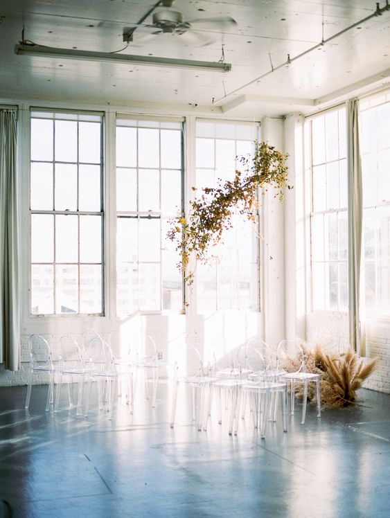 a minimalist fall wedding altar of bold fall leaves hanging over the space and some pampas grass on the floor plus ghost chairs