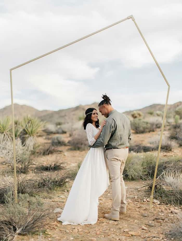 a minimalist geometric wedding arch placed right in the center of the desert is suitable for both a desert and a minimalist wedding