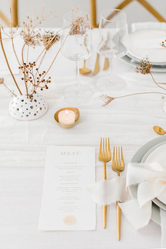 a minimalist neutral wedding table setting with white linens, grey plates and chargers, candles, gold cutlery and dried blooms