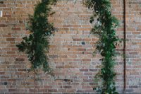 a minimalist organic wedding ceremony space with a greenery wedding arch and pillar candles on the floor