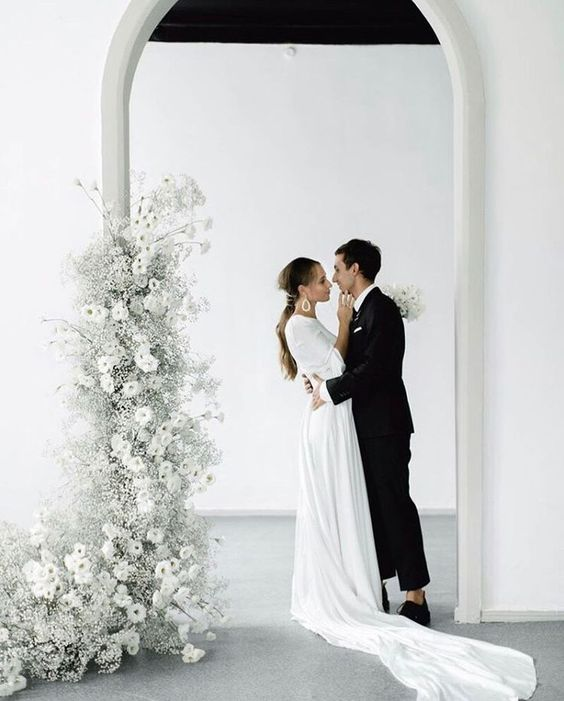 a minimalist wedding altar of a doorway decorated with ethereal white blooms, blooming branches and baby's breath is a gorgeous solution