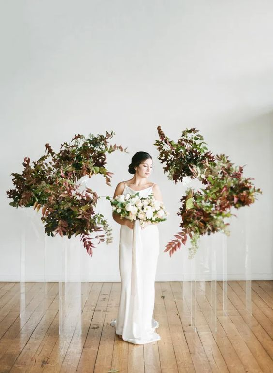 a minimalist wedding altar of acrylic stands with bold leaves and greenery is a beautiful idea for a fall minimalist wedding