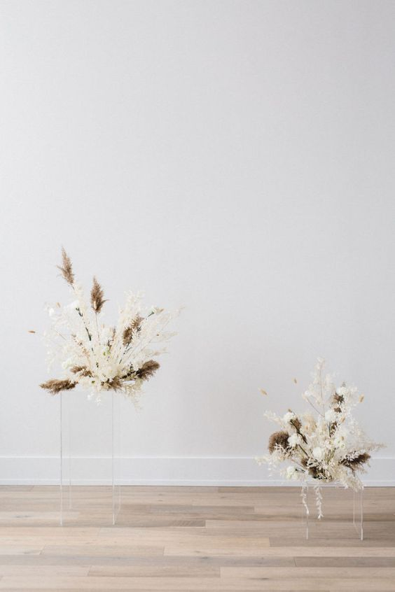 a minimalist wedding altar of white fresh blooms, dried foliage and grass arrangements on acrylic stands is a gorgeous solution