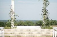 a minimalist wedding arch on a platform slightly covered with greenery and with a gorgeous view of the forest is amazing and lovely