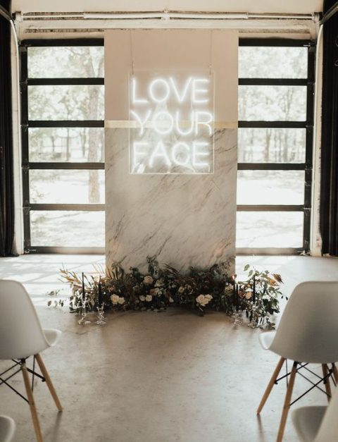 a minimalist wedding ceremony space done with a marble altar decorated with dried leaves, blooms and a neon sign