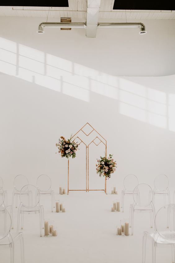 a minimalist wedding ceremony space with a geo wedding arch with pink floral arrangements, ghost chairs and pillar candles lining up the aisle
