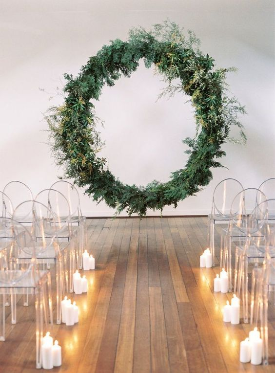 a minimalist wedding ceremony space with a giant greenery wedding wreath, sheer chairs and candles lining up the aisle
