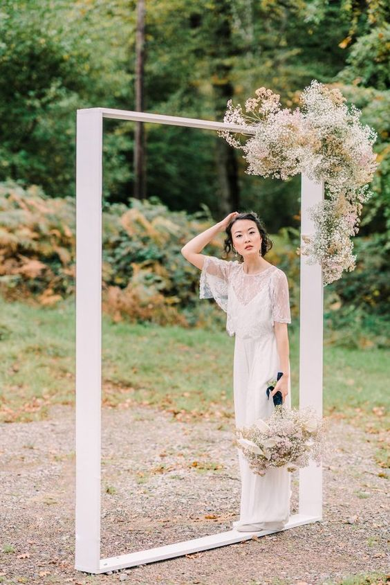 a minimalist wedding frame with some dried blooms and baby's breath is a bold and cool idea for a modern or minimalist wedding