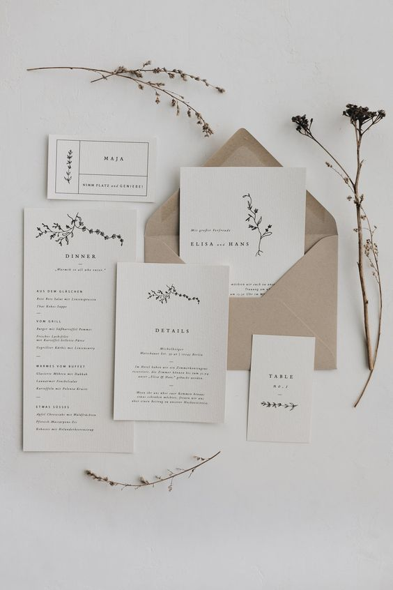 a minimalist wedding invitation suite in neutrals and with a kraft paper envelope, with black lettering and a bit of botanical prints