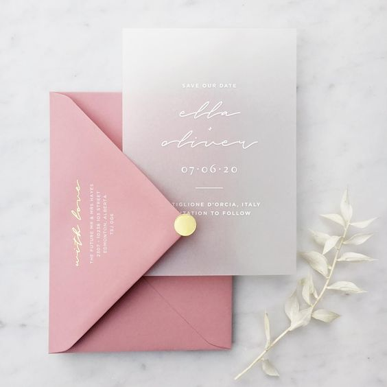 a minimalist wedding invitation suite with a pink envelope and a yellow button and a semi sheer invite with white calligraphy