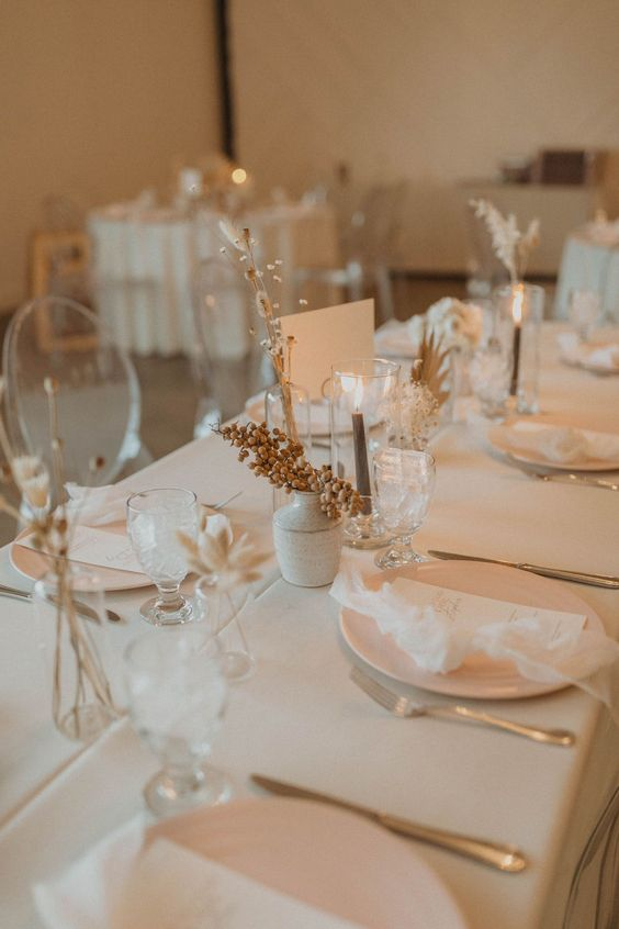 a natural and minimalist wedding table setting with all neutral everything, dried blooms, berries and grey candles is a stylish idea
