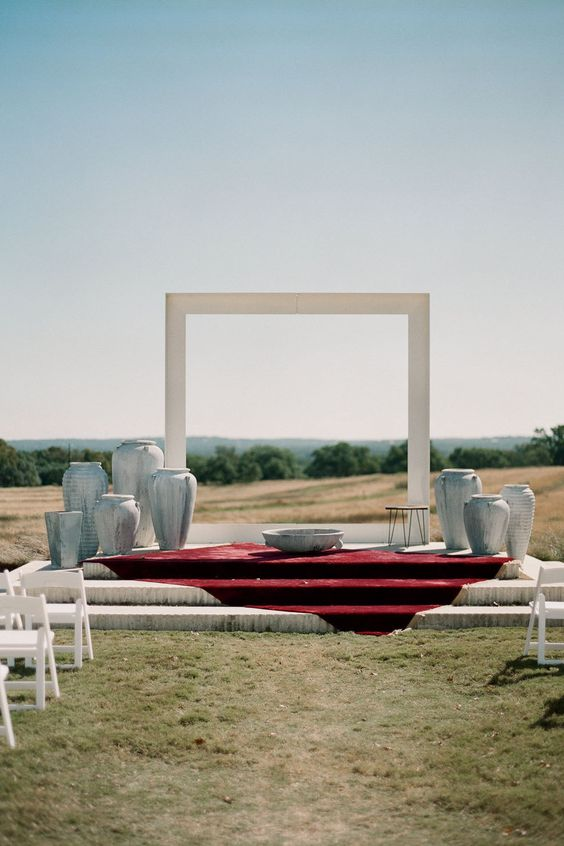 a natural backdrop with a minimalist white arch and vases around the arch to make a bold and cool statement
