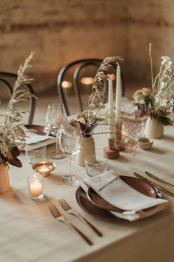 a neutral and delicate wedding tablescape with a greige tablecloth, brown porcelain plates and candleholders, greige vases and grasses