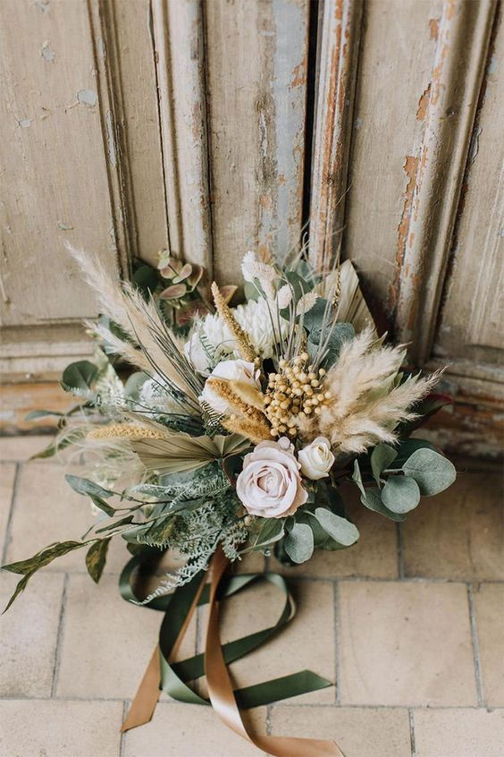 a neutral boho wedding bouquet of white and light pink blooms, pampas grass, greenery and foliage is a lovely idea for a boho bride