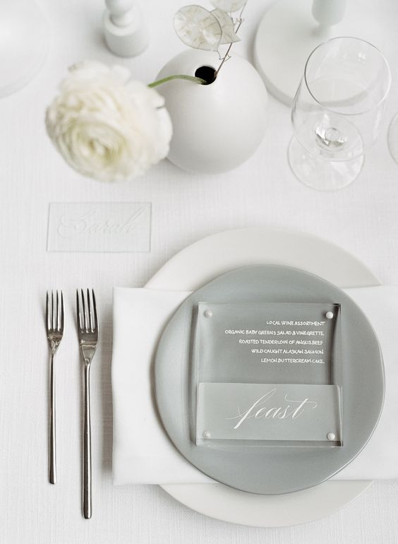 a neutral minimalist wedding table setting with white linens, a grey plate, white blooms in a round vase and simple cutlery