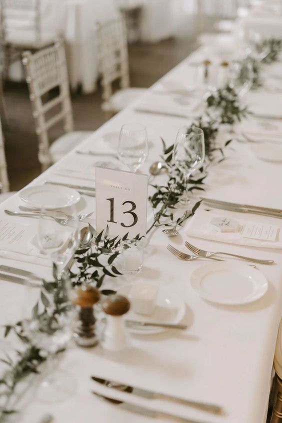 a neutral minimalist wedding tablescape with a greenery runner, all crispy white around and white menus is a cool idea
