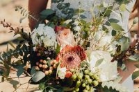 a neutral wedding bouquet of white and blush blooms, greenery, various types of berries is a lovely idea for a spring or summer bride