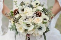 a pale winter wedding bouquet of white blooms, grey berries, greenery and pinecones is a very elegant and chic winter wedding arrangement