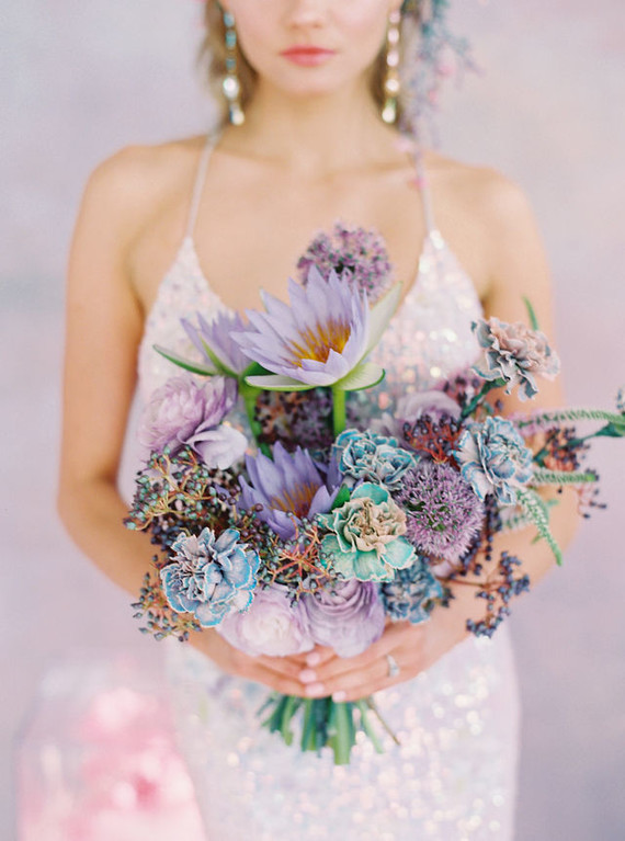 a pastel wedding bouquet with lilac, purple, blue and iridescent blooms, greenery and berries is a chic idea