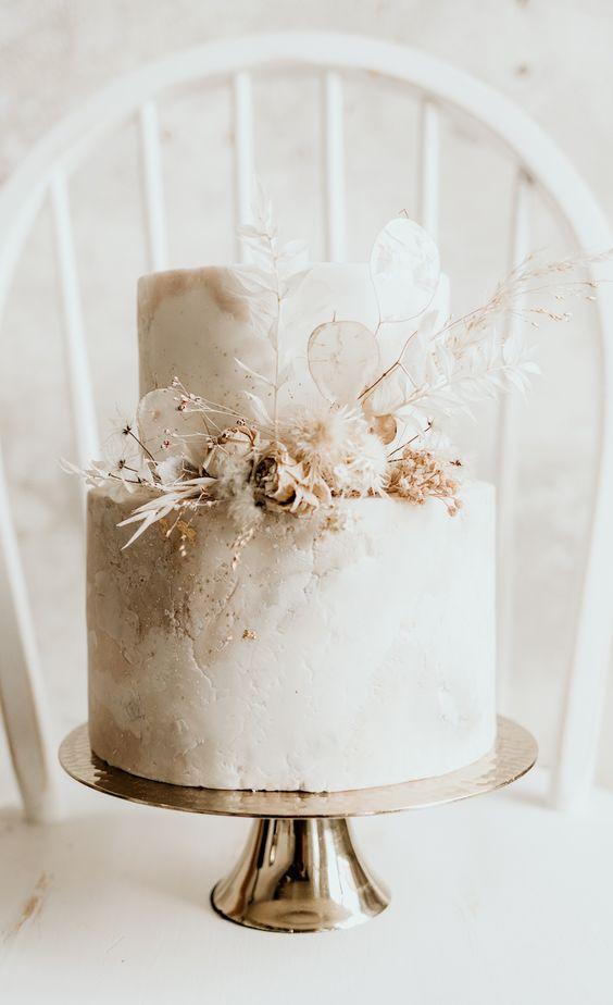 a patterned greige and white wedding cake decorated with metallic touches, dried blooms and grasses is a refined idea for a modern wedding