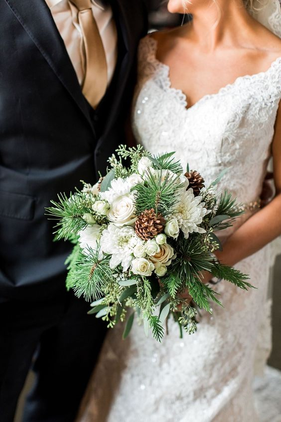 a pretty and chic winter wedding bouquet of white blooms, evergreens and pinecones is a simple and lovely idea for an elegant celebration