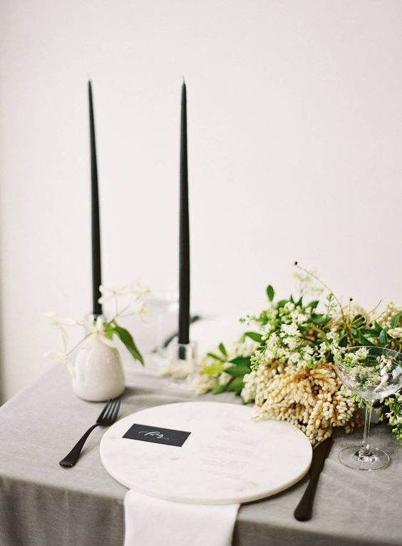 a pretty and elegant minimalist wedding tablescape with a grey tablecloth and white napkins, a marble charger, black candles and a greenery and white bloom centerpiece