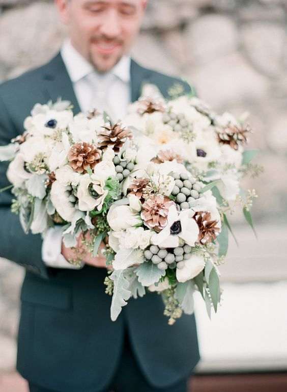 a pretty and lush winter wedding bouquet of white blooms, pale greenery, berries, pinecones is a cool idea for a winter wedding