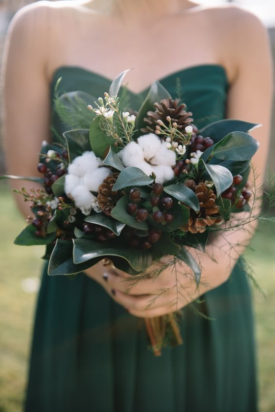 a pretty fall wedding bouquet of pinecones, berries, cotton, greenery and magnolia leaves is a gorgeous idea