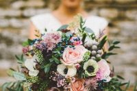 a pretty summer to fall wedding bouquet of pink, dusty pink and blush blooms, greenery and various types of berries is cool for the fall, too
