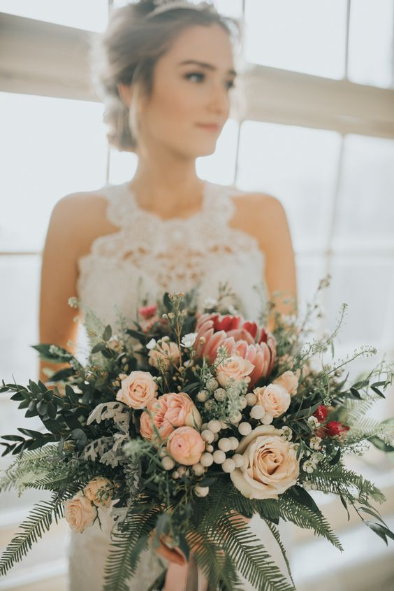 a pretty winter wedding bouquet of pink and blush blooms, berries and various kinds of greenery is a lovely idea for a winter bride
