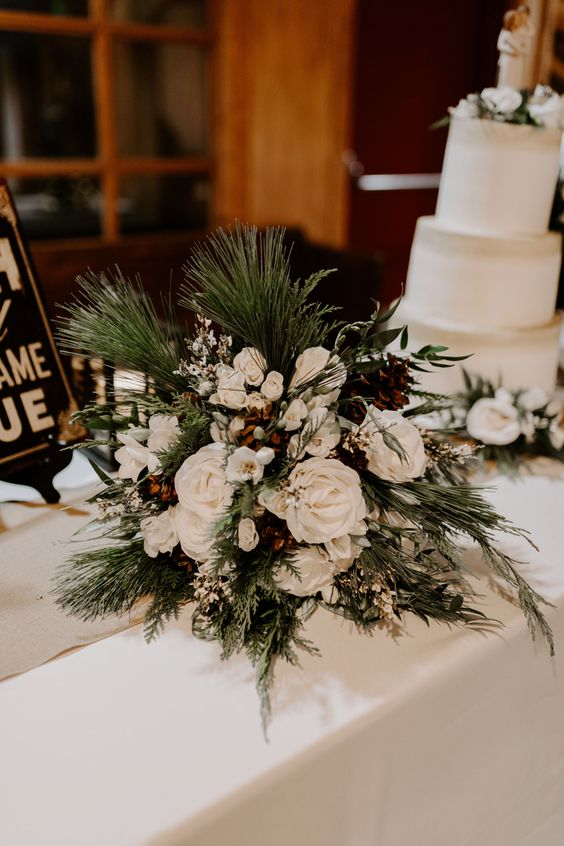 a pretty winter wedding bouquet of white blooms, evergreens, berries, pinecones is a lush and very textural idea for a rustic celebration