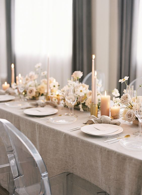 a refined and timeless wedding tablescape with a greige tablecloth, white and dusty pink blooms, pillar candles and white plates