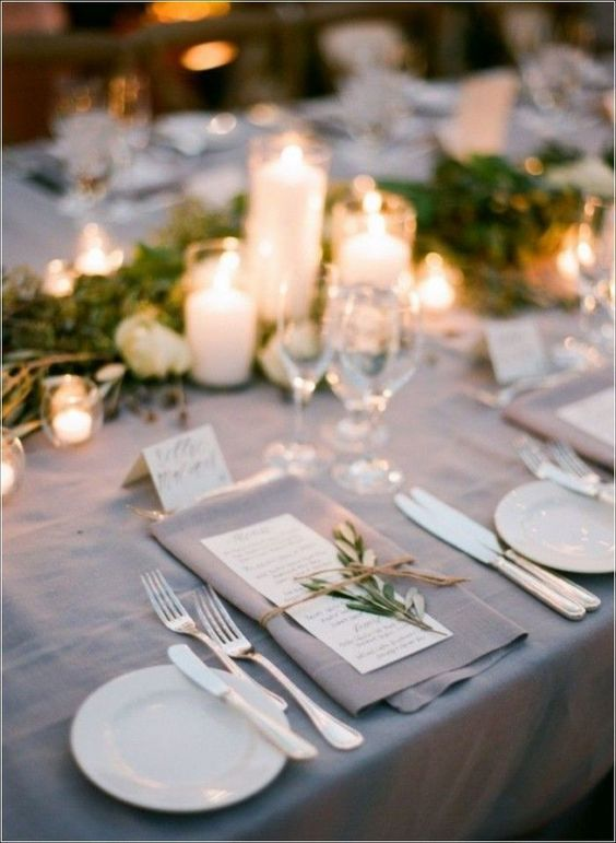 a refined greige wedding tablescape with a greenery runner, pillar candles, a greige napkin, white plates and cutlery